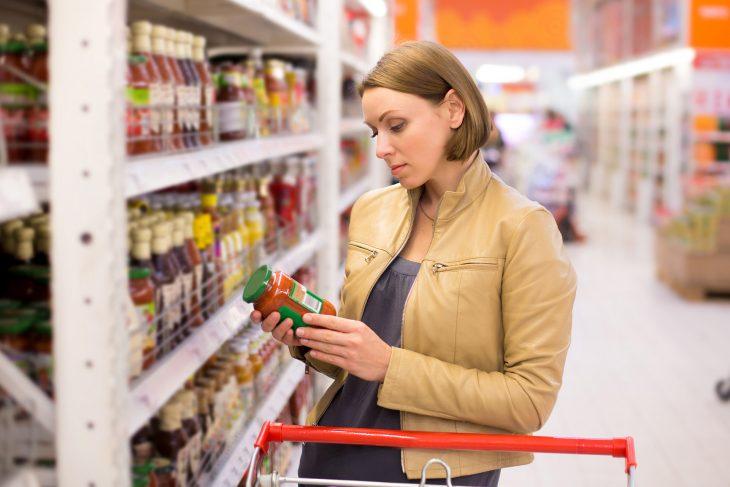 Mujer mira la etiqueta del frasco en supermercado
