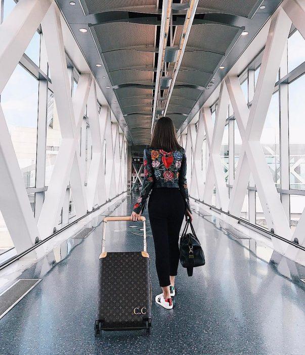 chica llevando su maleta por el pasillo del aeropuerto antes de viajar a Bélgica