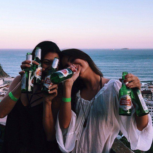 Amigas en la orilla de la playa bebiendo cerveza con ambas manos