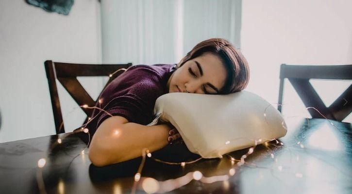 Chica recostada sobre la mesa usando la almohada Coodle Pillow para evitar entumecimiento del brazo