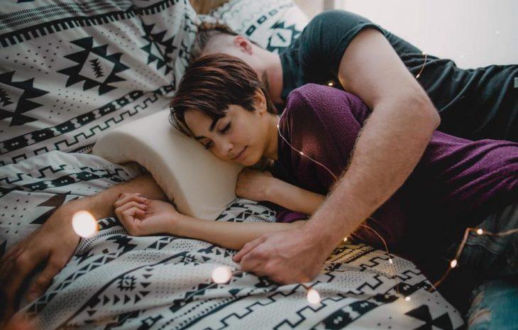 Pareja de novios recostados sobre una cama, abrazados de cucharita, usando la almohada Coodle Pillow