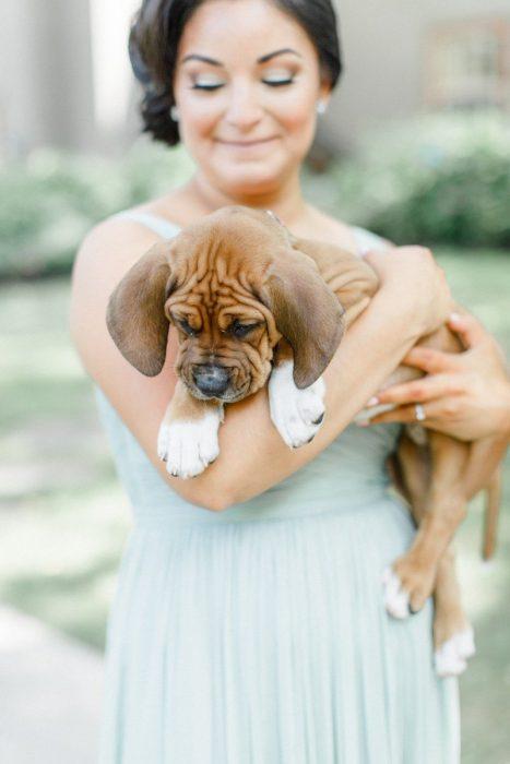 Dama de honor con vestido color menta sosteniendo a un cachorro en lugar de un ramo de flores