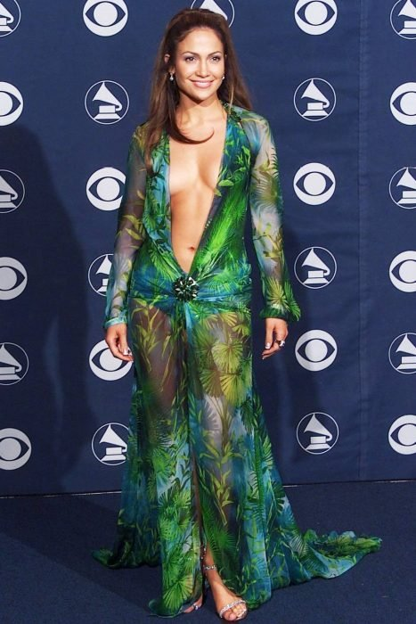 Jennifer Lopez usando vestido color verde con detalles en azul, dorado, transparencias, desfilando por la alfombra de los premios Grammy en el 2000