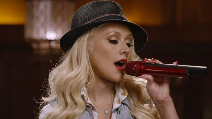Christina Aguilera con sombrero gris, maquillaje dorado, sosteniendo un micrófono rojo, cantando
