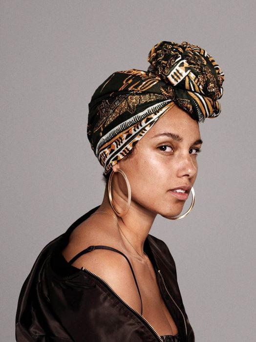 Alicia Keys mirando de perfil, con suetér negro, blusa de tirantes, mascada en la cabeza, arracadas grandes