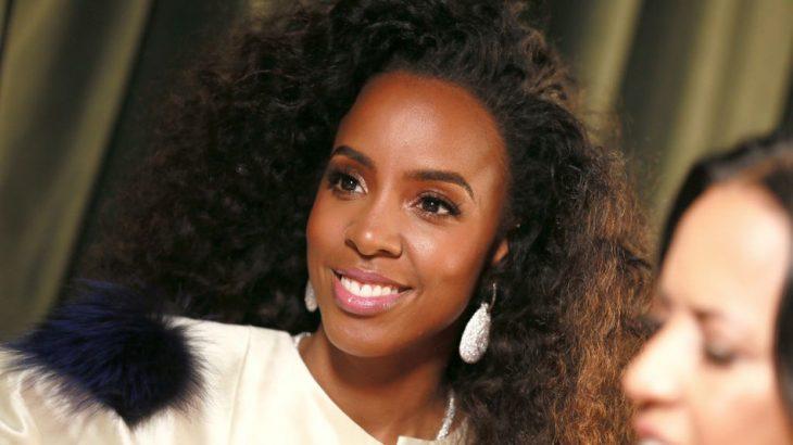 Kelly Rowland sonriendo, con cabello largo y rizado, llevando pendientes grandes y blancos