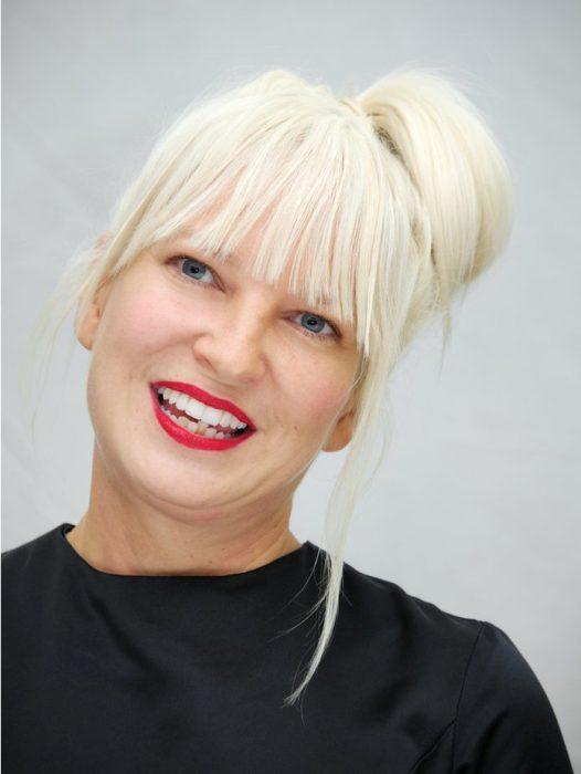 Sia , mujer con cabello rubio platinado, flequillo, recogido en bun, labios rojos, con la cabeza inclinada hacia su hombro izquierdo, llevando suéter negro