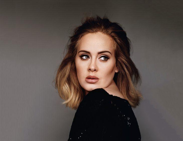 Adele con fondo gris, de perfil, vestido negro, posando para una fotografía, con cabello midi balayage