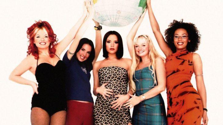 Las Spice Girls dentro de una habitación blanca, posando para una fotografía con las manos arriba, sonriendo, acomodadas en medio circulo