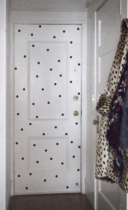 Puerta blanca de un armario decorada con puntos de color negro