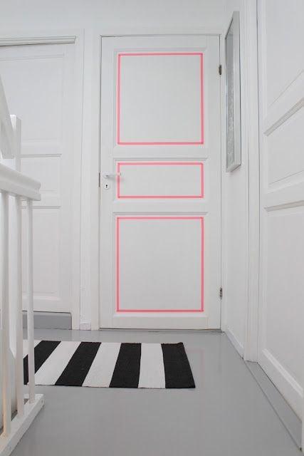 Puerta blanca decorada con líneas de color rosa en los cuadros que la forman