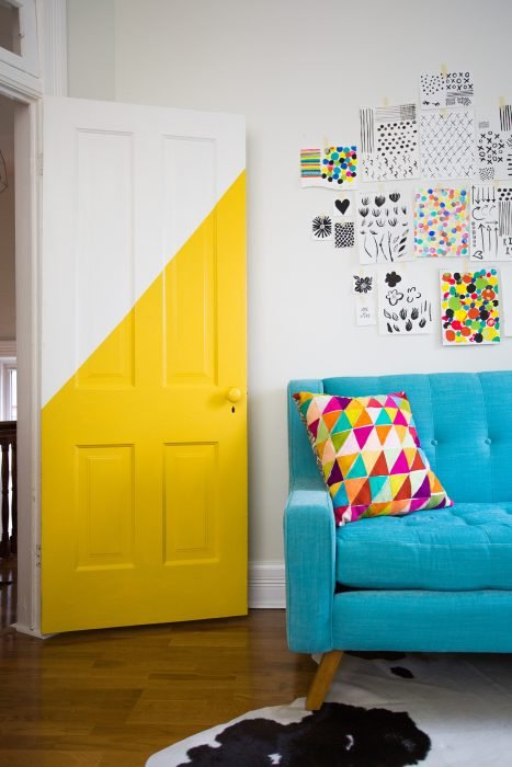 Door of a room that is on the side of a blue sofa decorated in half with yellow paint