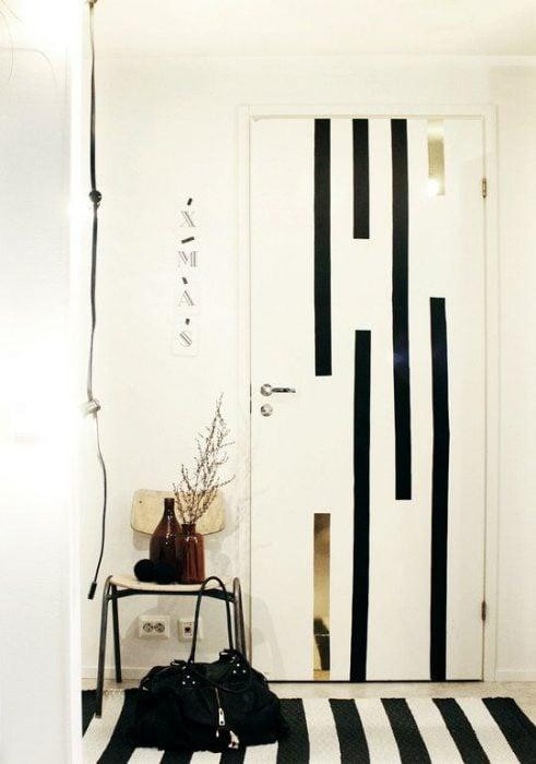 Puerta de una habitación decorada con líneas de color negras que combinan con la alfombra de la habitación