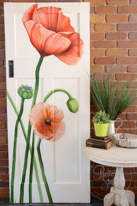 Puerta de una habitación decorada con flores pintadas a mano