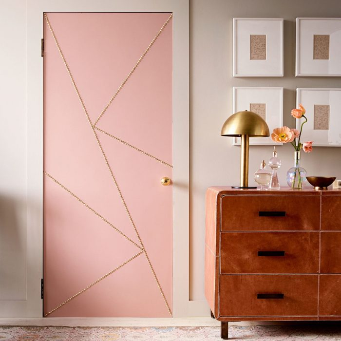 Door of a room that is next to a showcase and some pictures painted of pink color and decorated with lines of golden color