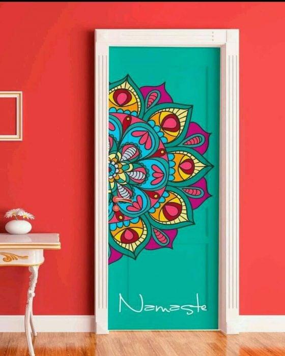 Puerta de una habitación decorada con un mandala de colores y abajo la frase namaste