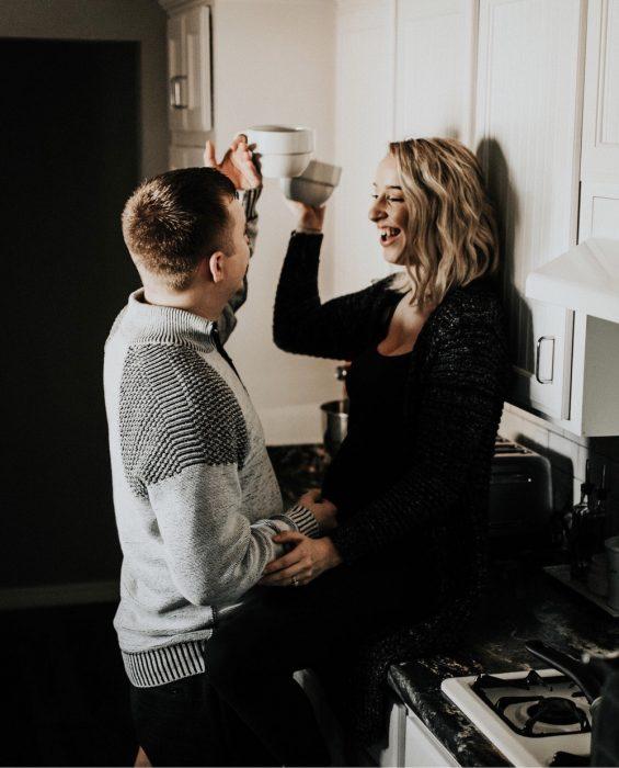 Par de novios chocando sus tazas de café, sonriendo, charlando en la cocina