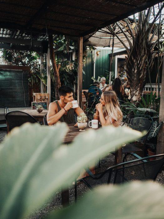 Pareja d enovios bebiendo café en un restaurante sobre la playa