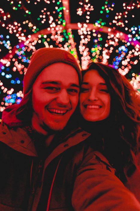 Pareja de novios tomando una selfie de ellos en una feria de pueblo con luces de colores