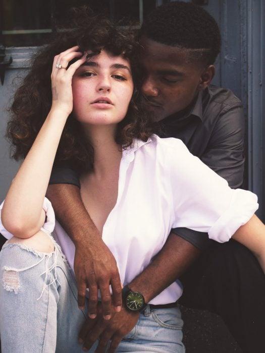 Pareja interracial abrazados, sentados en un portico de madera, posando para una fotografía
