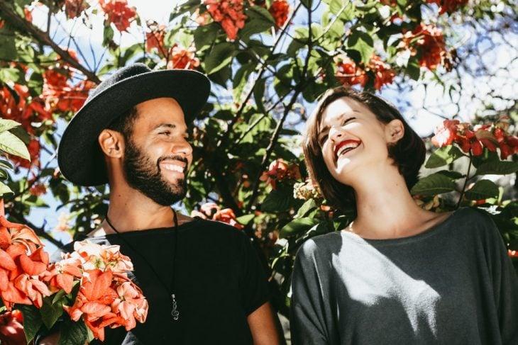 Pareja de novios bajo las ramas de un cerezo en flor, sonriendo y posando para una foto