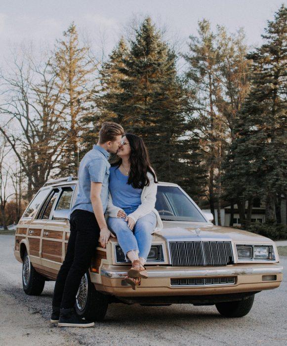 Chica sentada sobre el cofre de un automóvil, mientras es besada por su novio a mitad de carretera