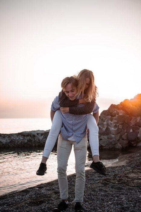 Chico cargando a una chica sobre su espalda a la orilla del mar en la playa
