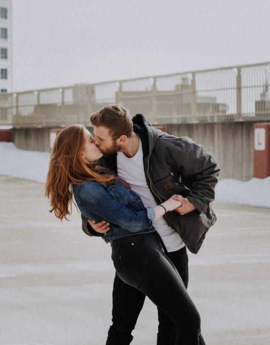 Pareja de novios bailando y besándose a mitad de la calle