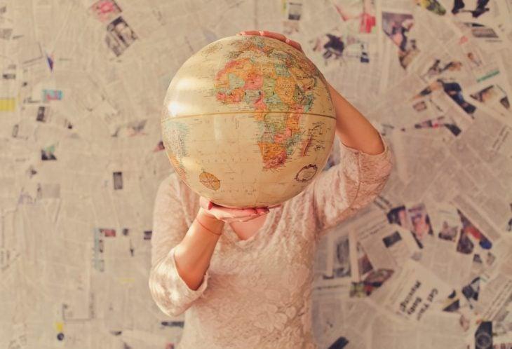 Mujer con blusa blanca de manga larga, sosteniendo un globo terraqueo entresus manos, cubriendo su rostro con el, mirando el país de escocia donde recetan viajes en la naturaleza