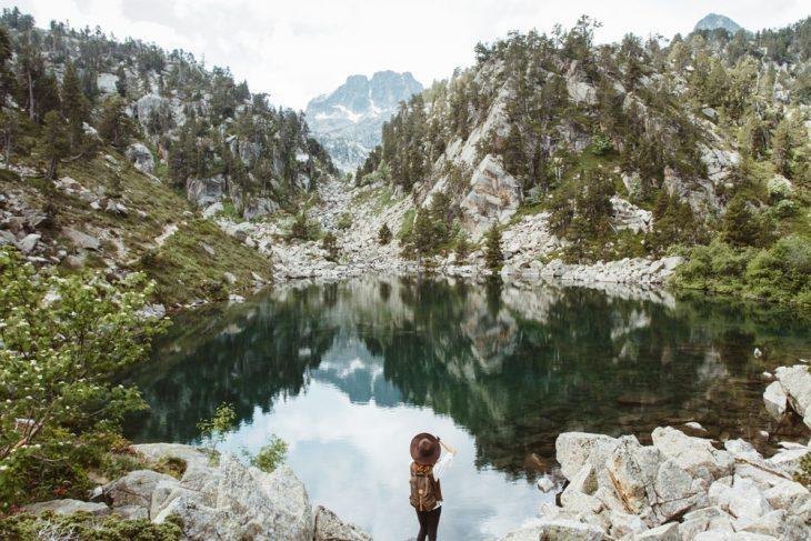 Chica con mochila y sombrero café, parada en la orilla de un lago, mirando al horizonte entre montañas y nubes de escocia donde los doctores recetan viajes en la naturaleza