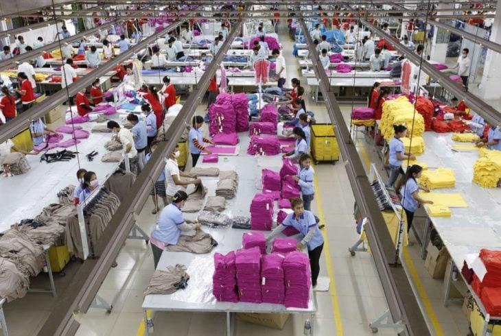 Fabrica textil, mujeres trabajando en maquinas de coser industriales dentro de una fabrica de ropa, escena del documental The True Cost