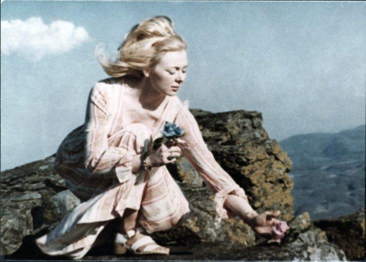 Joyce McKinney, chica parada sobre unas rocas a la orilla del mar usando maxivestido rosa con mangas largas, siendo golpeada por la brisa del mar, escena del documental Tabloid
