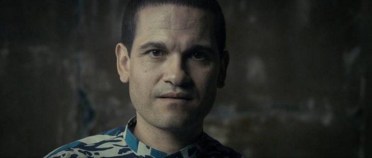 Nicholas Barclay, hombre con nariz chata, ojos pequeños, piel morena, cejas delgadas, mirando de frente, parado en un cuarto de cemento, escena del documental The Imposter