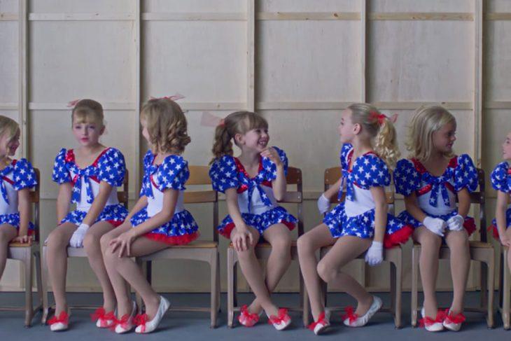 escena del documental Casting JonBenet, Grupo de niñas usando vestidos azul marino con puntos blancos, guantes blancos, zapatos rojos, sentadas en sillas, dentro de una sala de espera