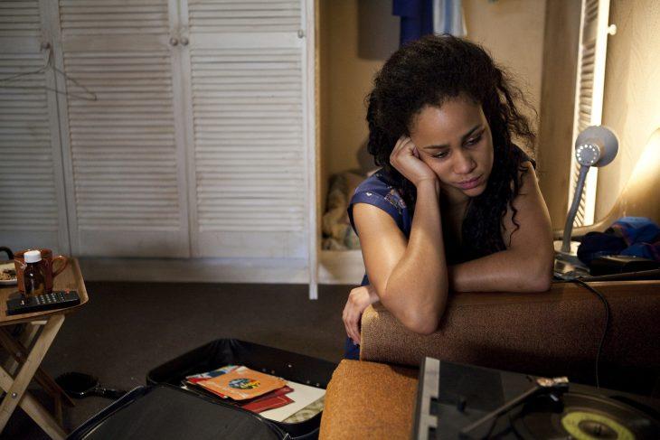 Joyce Vincent, chica sentada sobre la alfombra dentro de su recamara con closet blanco, recargada en la orilla del sofá, cabizbaja, mirando hacia abajo, con el rostro recargado sobre su mano derecha, escena del documental Dreams of a Life
