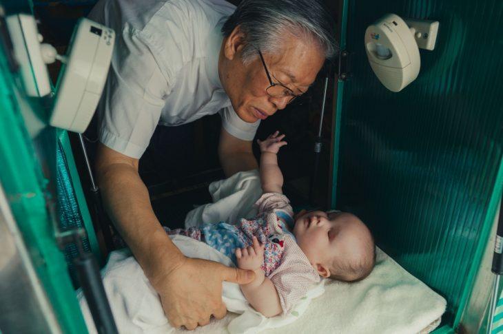 Hombre adulto con rasgos asiáticos inclinado para levantar a un bebé que se encuentra en un contenedor metálico, escena del documental The Drop Box