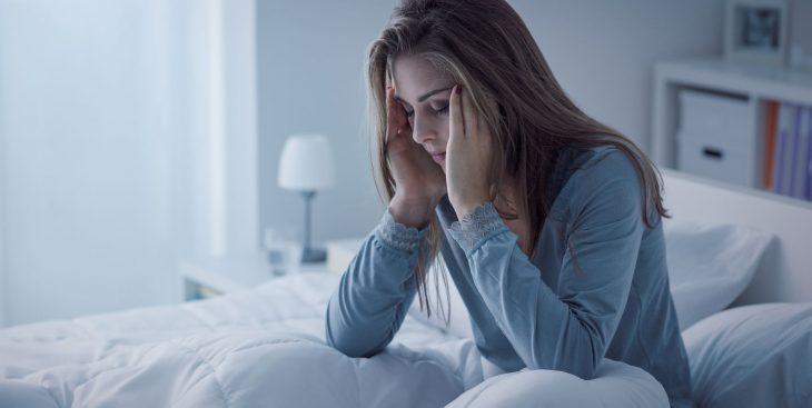 Chica tocando sus cienes con los ojos cerrados , la cara hacia abajo, con dolor de cabeza, sentada en una cama con sabanas bancas