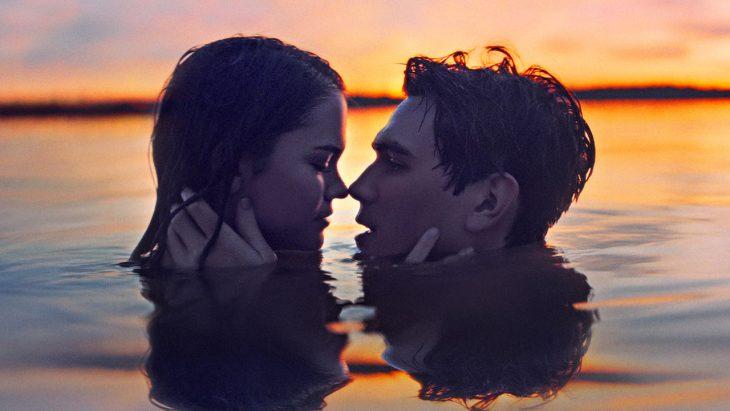 Pareja dentro de un lago mirándose fijamente a los ojos, escena de la película Nuestro último verano