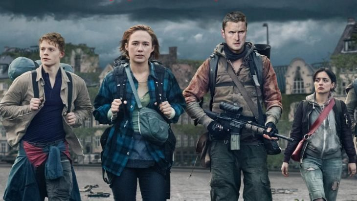 Grupo de adolescentes llevando mochilas de viaje y amaras sobre sus hombros para enfrentarse a su enemigo en medio de una ciudad desértica, escena de la serie The Rain