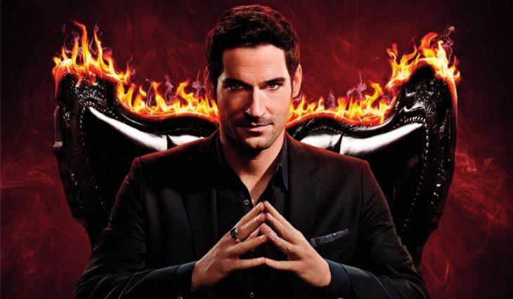 Hombre con traje sastre negro cruzando las manos sentado en una silla con llamas, escena de la serie Lucifer
