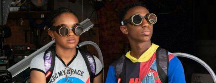 Hermanos mellizos llevando una mochila metalica en sus hombros y un par de anteojos oscuros sobre ellos, escena de la película Nos vemos ayer