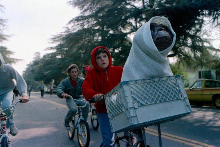 Niños paseando en bicicleta llevando un muñeco de pelucho de un extraterrestre en una cesta, escena de la película E.T., el extraterrestre