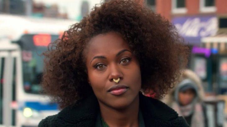 Mujer afroamericana con un piercing en la nariz y gesto molesto mirando hacia el frente, escna de la serie She's Gotta Have It