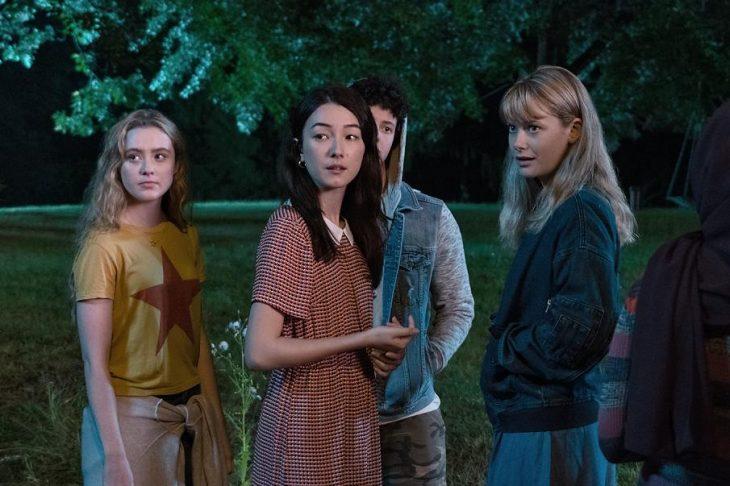 Grupo de adolescentes reunidos en un patio durante una fiesta de preparatoria, escena de la serie The Society