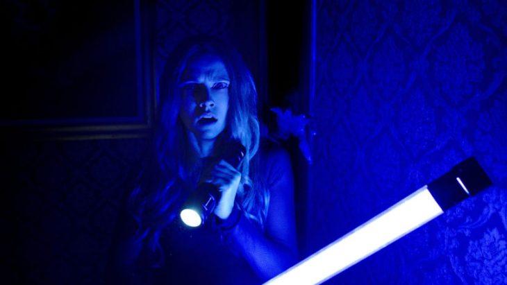 Mujer temerosa sosteniendo una lampara de luz led entre sus manos escena de la película Cuando las luces se apagan