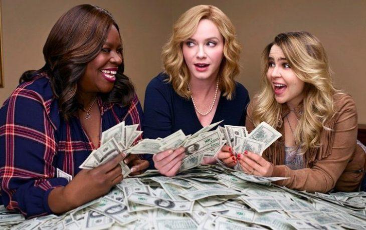 Mujeres reunidas alrededor de una mesa sosteniendo dinero entre sus manos, mirándose sorprendidamente entre sí, escena de la serie Chicas buenas