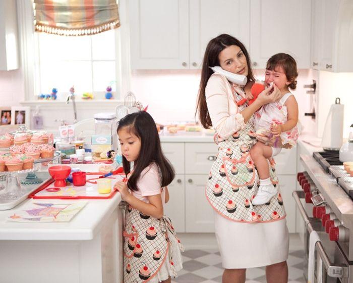 Madre sosteniendo a su bebé en brazos mientras habla por teléfono y su otra hija sobre la mesa viendo unos cupcakes