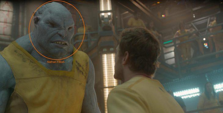 Hombre mirando a un extraterreste de colro azul a los ojos, escena de la película Guardianes de la Galaxia, Nathan Fillion, Chris Pratt
