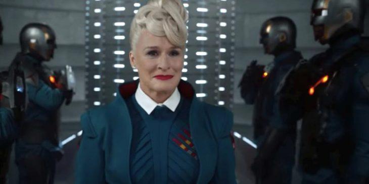 Mujer adulta caminando por un pasillo lleno de luces, rodeada de robots, escena de la película Guardianes de la Galaxia, Glenn Close