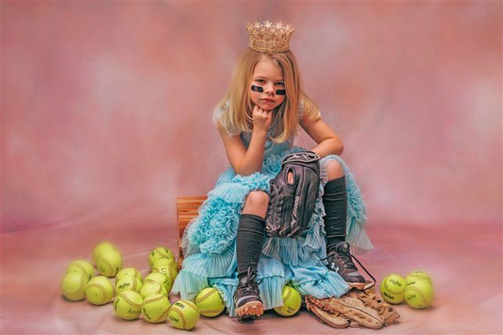 Niña con vestido azul estilo princesa sentada en una reja de madera rodeada de pelotas de tenis, fotografía por Heather Mitchell